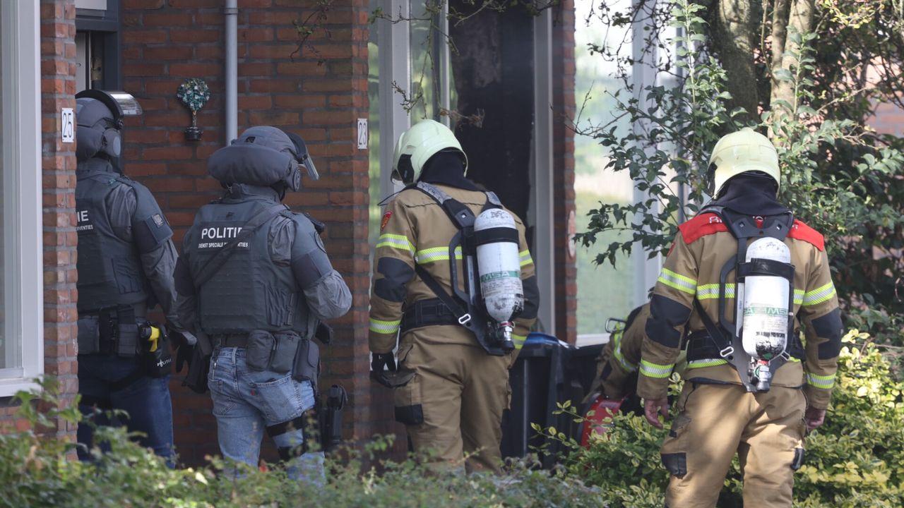 Arrestatieteam en brandweer voorzichtig uit angst voor vuurwapens in brandend huis