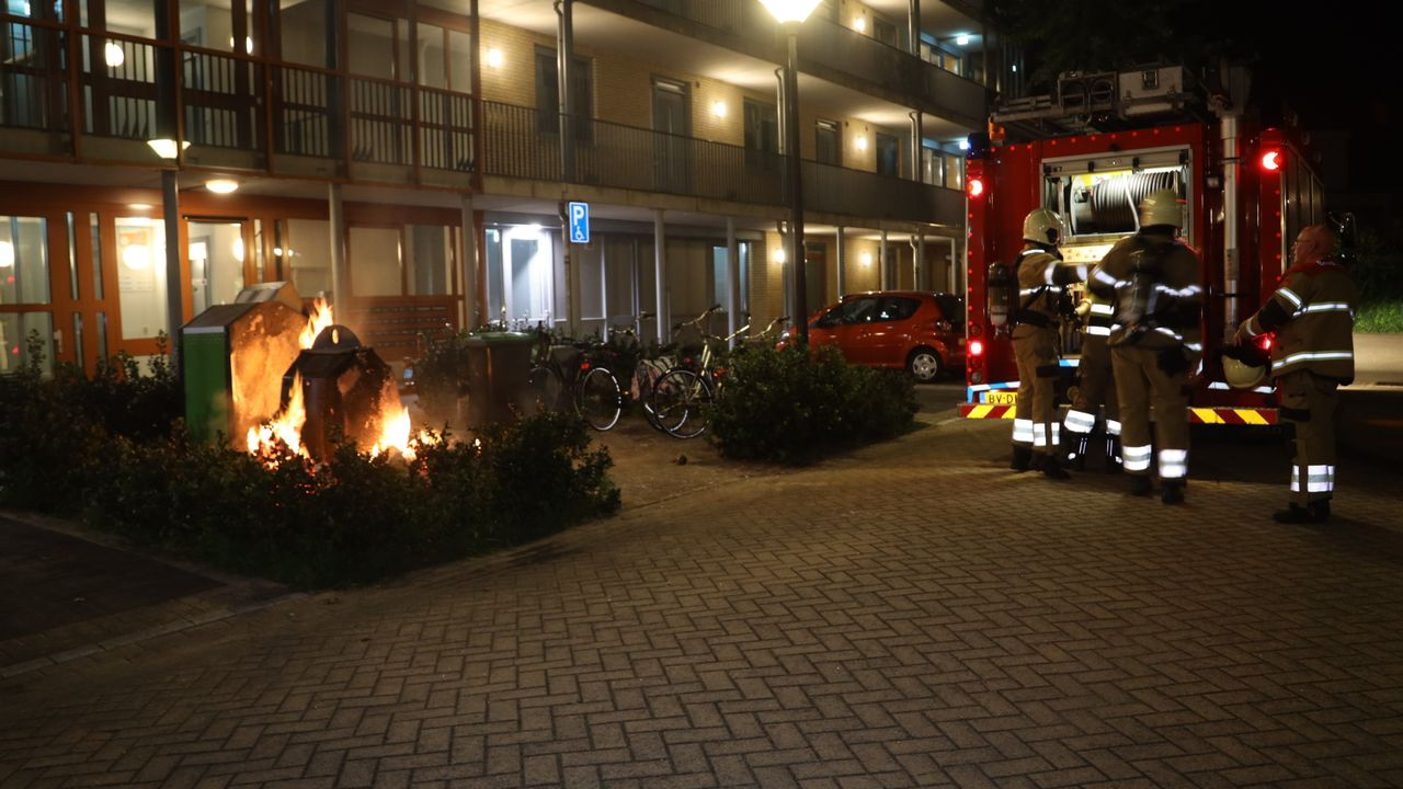 Oud papier naast container in brand
